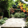 sunny paved garden with terracotta planted pot Mile End thumbnail